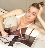 Bored woman sick in bed. Attractive young bored woman sick in bed with a magazine and drink staring upwards lost in thought daydreaming Stock Images
