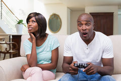 Bored woman sitting next to her boyfriend playing video games Stock Images