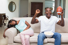Bored woman sitting next to her boyfriend watching football Royalty Free Stock Photography