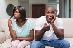 Bored woman sitting next to her boyfriend watching tv Stock Photos