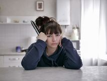 Bored woman sitting with remote control on a blurred background of the kitchen stock images