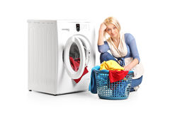 Bored woman sitting by a washing machine Royalty Free Stock Photography