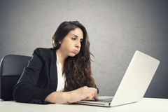Bored woman snorts in the office while working on the laptop royalty free stock photos