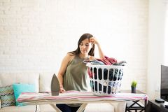 Bored woman standing behind iron board. Disappointed unhappy housewife leaning on a pile of laundry on the ironing board Stock Photo