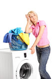 Bored woman standing by a washing machine Royalty Free Stock Image