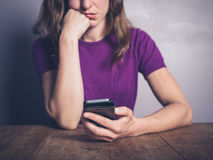 Bored woman using smartphone at table Royalty Free Stock Photos