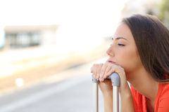 Bored woman waiting for delayed transportation. In a train station Royalty Free Stock Photo