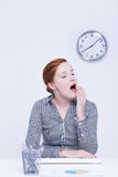 Bored woman at work. Bored and unprofessional woman at work in office yawns Stock Image