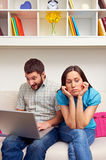 Bored woman sitting while her boyfriend Stock Image
