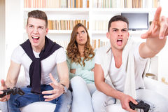 Bored women between two casual passionate men playing video game Royalty Free Stock Image