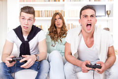 Bored women between two men with joystick. Pretty bored women between two casual men playing video game with joystick Royalty Free Stock Photo