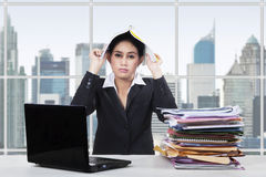 Bored worker puts paperwork on her head Stock Photo