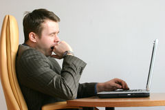 Bored,yawning businessman. Bored, yawning businessman sitting with his laptop at the desk stock photos