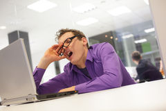 Bored yawning businessman working with laptop. Supporting his head on his hand in office space Stock Photography