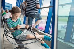 Bored 7 years old boy child waiting for his plane Royalty Free Stock Images