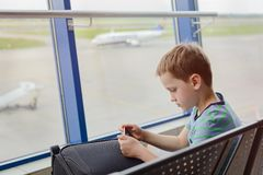 Bored 7 years old boy child waiting for his plane Stock Photo