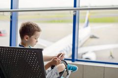 Bored 7 years old boy child waiting for his plane Stock Image