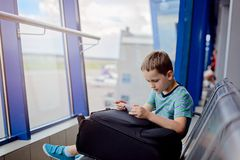 Bored 7 years old boy child waiting for his plane Royalty Free Stock Image