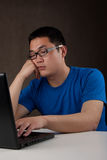 Bored young asian man working with his computer Stock Image