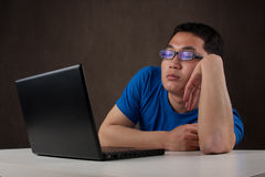 Bored young asian man working with his computer Stock Photo
