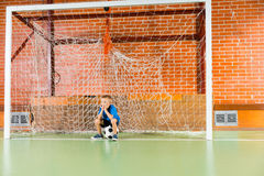 Bored young boy waiting on an indoor soccer court Royalty Free Stock Photo