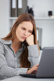 Bored young business woman working with laptop. Royalty Free Stock Images