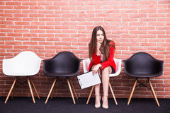 Bored young businesswoman holding paper and looking away while sitting on chair Stock Images