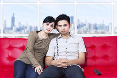 Bored young couple watching television at apartment Stock Photos