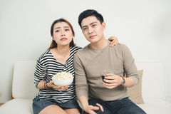 Bored young couple watching television at home Stock Photography