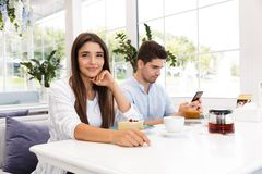 Bored young girl sitting at the cafe table. Smiling young girl sitting at the cafe table while her boyfriend using mobile phone royalty free stock image