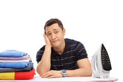 Bored young guy ironing clothes Stock Image
