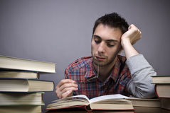 Bored young man reading a book Royalty Free Stock Image