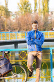 Bored young man standing waiting. With folded arms leaning back against colorful iron railings above a lake or canal with his bike alongside Royalty Free Stock Images