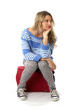Bored Young Woman Sitting on a  Red Suitcase Royalty Free Stock Images