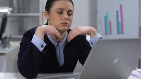 Bored young woman typing laptop sitting table, office work routine, tiredness stock footage