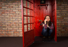 Bored young woman waiting for a call. In a public telephone booth sitting on the floor with a grumpy expression Stock Photos