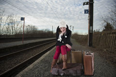 Bored young woman in winter clothes waiting for her train Stock Photo