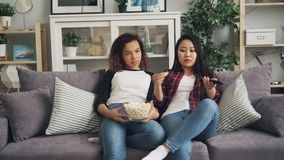 Bored young women are watching TV together at home and eating popcorn sitting on sofa in living room. Asian girl is