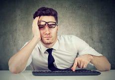 Bored zitting van de mensenwerknemer bij bureau heeft geen motivatie te werken stock afbeelding