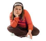 Boredom. A young girl sitting on the floor crosslegged and looking bored, isolated against a white background Stock Photo