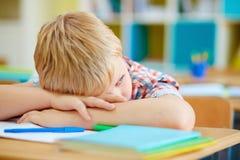 Boredom. Bored schoolboy sitting at lesson Stock Photo