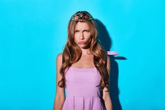 Boredom. Disappointed young woman in tiara looking at camera while standing against blue background stock photography