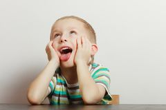 Kid making funny faces being bored. Boredom, face expression concept. Little boy making funny faces being bored, he wants to play with somebody Royalty Free Stock Photography