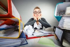 Bored sleepy businesswoman in office. Boredom and fatigue concept. Young emotional expressive woman in office. Bored tired businesswoman with paper ball at work Royalty Free Stock Photography