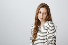 Boredom kills me inside. Upset indifferent cute girl with long fair hair standing half-turned and looking aside with. Uninterested expression, being tired and royalty free stock image