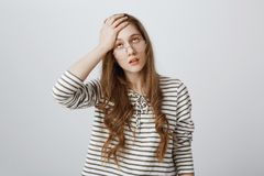 Boredom kills me. Portrait of annoyed and tired attractive woman rolling eyes and holding palm on forehead, expressing. Irritation of hearing boring Royalty Free Stock Photo