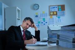 Boredom mature businessman. Portrait Of Boredom Mature Businessman With Stack Of Folders Stock Photos