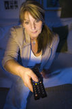 Boredom on the TV. Mature woman with remote control on the Couch in a dark room Stock Image