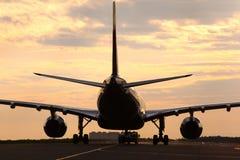 Borgerlig trafikflygplan som bogserar med lastbilen på gryning Royaltyfria Bilder