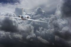 Borgerligt trafikflygplanhuvud till åskvädermoln royaltyfria bilder